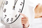 picture of pressure point  - Young business woman pointing on a clock and time - JPG