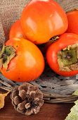 Ripe persimmons with bump on table on sackcloth background