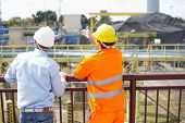 stock photo of headgear  - Back view of architects inspecting construction site - JPG