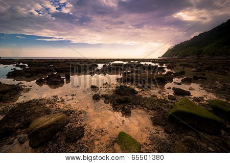 Sunset At Tropical Beach With Rocks And Stones