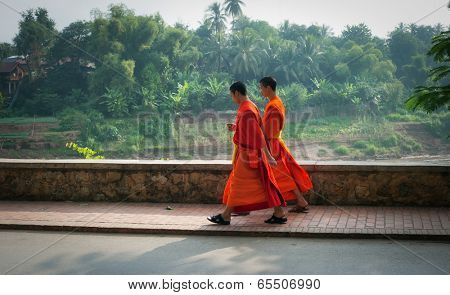 LUANG PRABANG, LAOS - 8 DEC, 2013: Two unidentified young monks passing the street of city. Luang Prabang is one of most popular tourist destinations in Laos