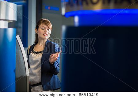 Pretty, young woman withdrawing money from her credit card in at an ATM (shallow DOF; color toned image)