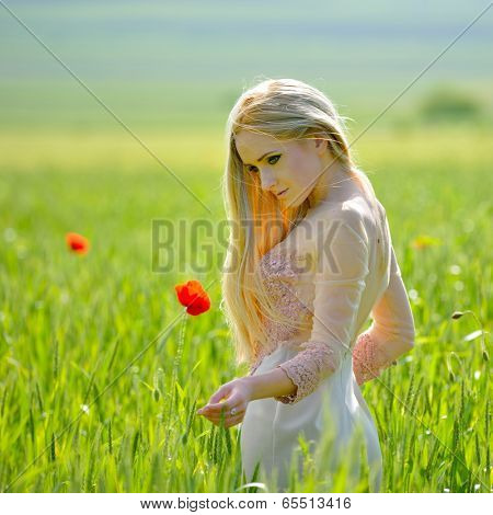 Beautiful girl on blooming poppy field i spring
