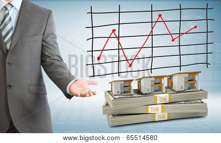 Businessman points hand on houses and money