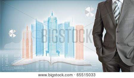 Businessman with high-tech skyscrapers and graphs