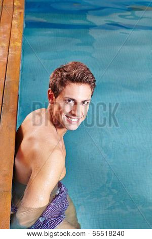 Smiling young man standing on edge of swimming pool
