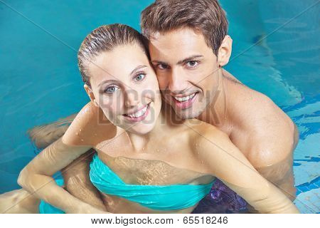 Smiling happy couple sitting in water of a hotel swimming pool