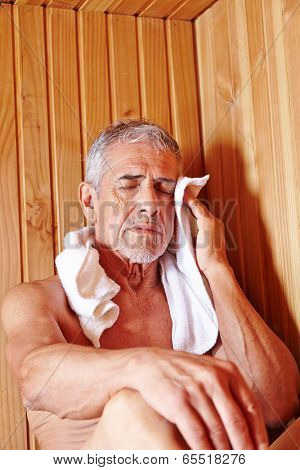 Old man with towel sweating in sauna of spa hotel