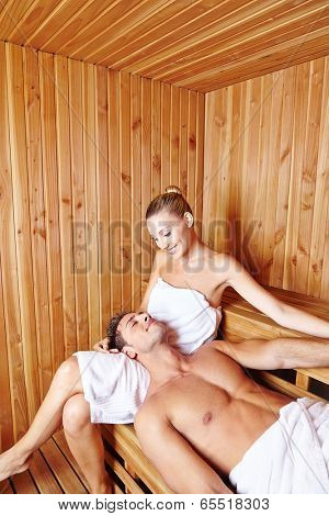 Happy young couple relaxing together in the sauna of a hotel