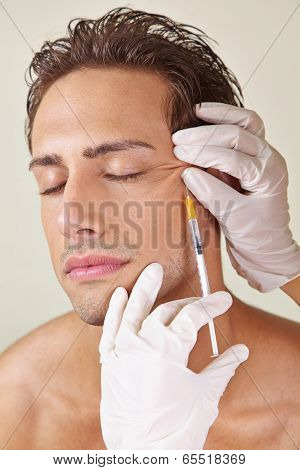 Man having crows feet removed in a beauty clinic with hyaluronic acid