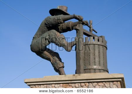 Statue of a man making wine