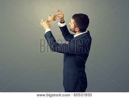 young businessman scrutinizing banknote over dark background