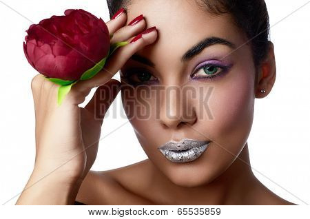 Closeup of woman's face with silver lipstick. Blue contact lenses, purple eye shadows and tanned hand with red metallic and texture manicure holding red fabric flower