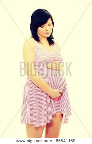 Pregnant teen woman portrait holding her belly