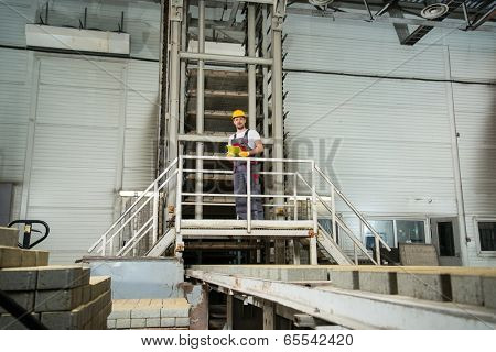 Man in a safety hat taking notes on a factory