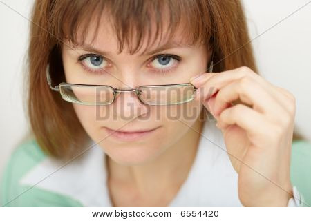 Young Woman Strictly Looks Over Spectacles