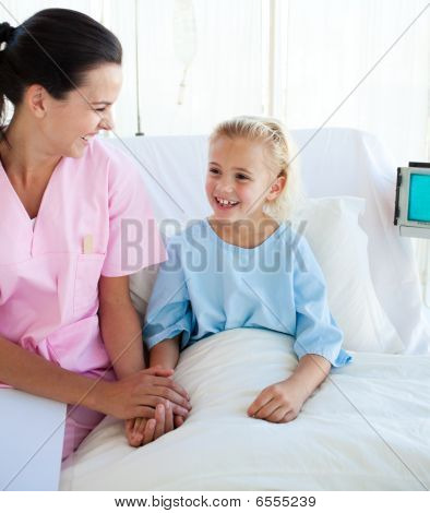 Smiling Little Girl Sitting On A Hospital Bed With Her Doctor