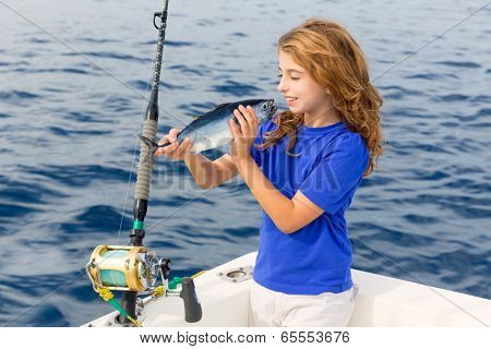Blond girl fishing bluefin tuna trolling in Mediterranean sea catch and release