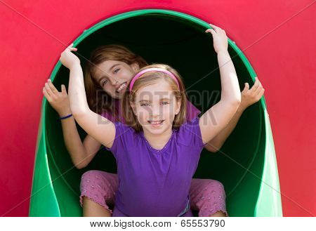 kid sister girls playing in the park playground tunnel