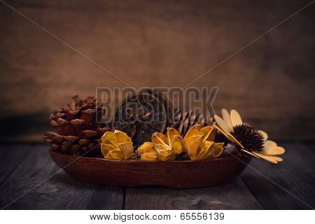 Aromatherapy concept. Dried flowers on wooden bowl in low light ambient setting.