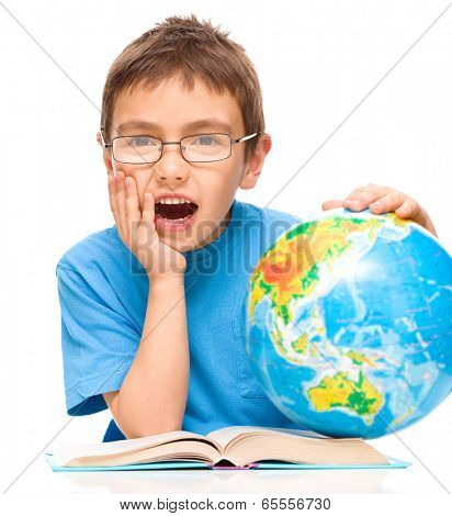 Little boy is holding his face in astonishment while sitting at table with globe, isolated over white