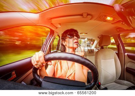 Women make up lips at the wheel the car, not stares on the road creating an emergency situation.