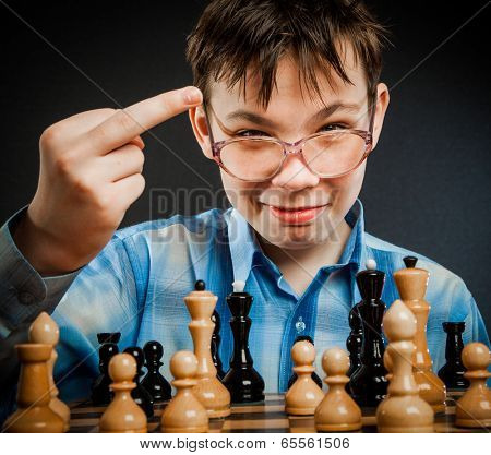 Wunderkind play chess. Funny Nerd boy. Shows the middle finger to the opponent.