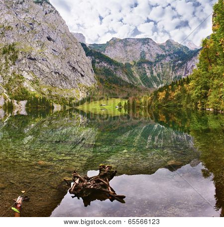 Cloudy day on the lake. Magic reflection in German lake Koenigssee. Clouds and mountains reflected in the mirrored surface of the water