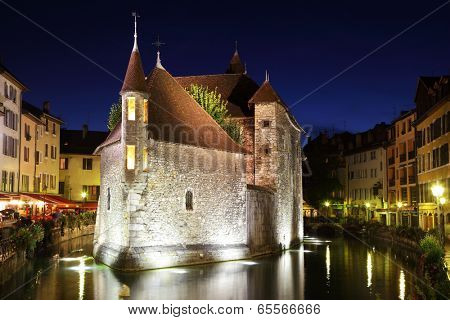 ANNECY, FRANCE - SEPTEMBER 16, 2012: The capital of the Haute-Savoie - Annecy. The ancient fortress-prison on island in  middle of river. Fortress beautifully lit and reflected in the dark water