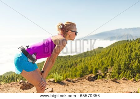 Young Woman Running In Mountains On Sunny Summer Day