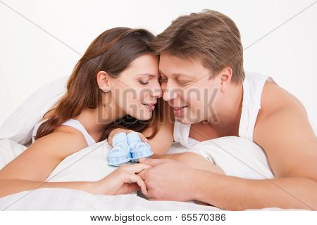 happy young pregnant woman with husband on bed