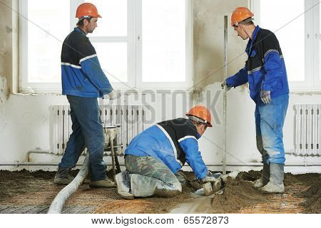 Plasterer workers at indoor concrete cement floor topping with float