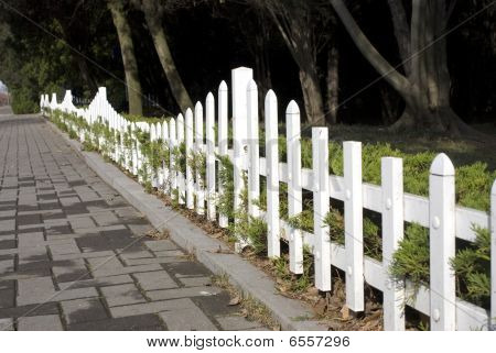 Beautiful white fence of the garden in late autumn