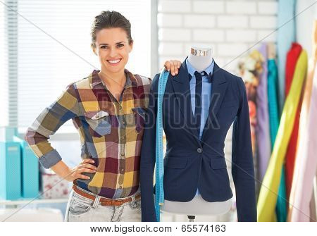 Portrait Of Smiling Seamstress Near Mannequin In Suit