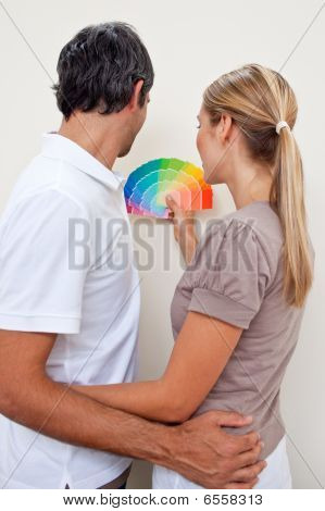 Happy Couple Choosing A Color With To Paint Their Bedroom