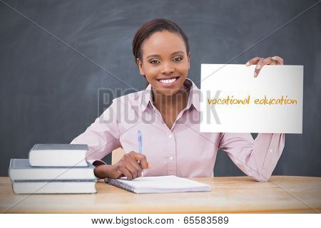 Happy teacher holding page showing vocational education in her classroom at school