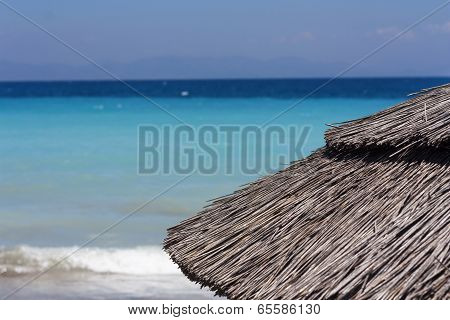 Straw Umbrella On Beautiful Tropical Beach. Parasol Near Sea And Mountain Photo.