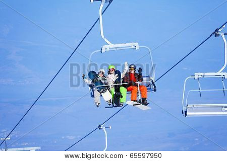 Three young people with snowboarders on ropeway