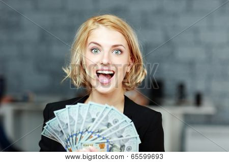 Young businesswoman holding money with delight