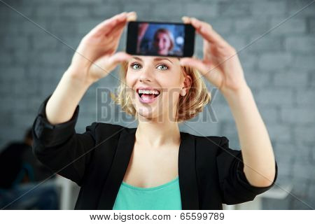 Young laughing woman making a self photo by her smartphone in office