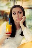 stock photo of pouting  - Bored young woman with a cocktail drink on a sunny day