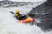 foto of rough-water  - an active male kayaker rolling and surfing in rough water - JPG