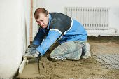 pic of floor covering  - Plasterer at indoor concrete cement floor topping with float - JPG