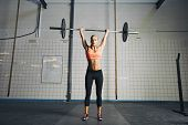 picture of snatch  - Full length image of strong young woman with barbell and weight plates overhead doing crossfit exercise. Fit female athlete lifting heavy weights.