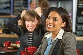 picture of outrageous  - Smiling woman in coffee house with frustrated friend - JPG