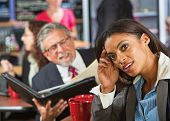 stock photo of disrespect  - Bored woman next to man working during lunch break - JPG