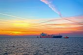 picture of fuel tanker  - Tanker and tugboat on sea early morning just before sunrise - JPG