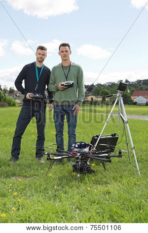 Portrait of confident engineers holding remote controls of UAV helicopter at park