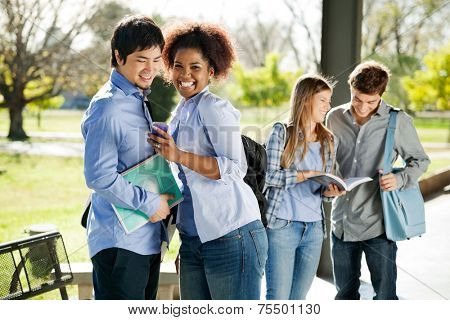 Portrait of cheerful female student showing cellphone to friend while classmates standing in background at college campus