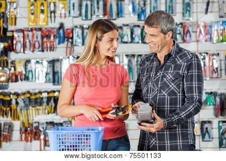 Smiling couple looking at each other while paying for pliers through smartphone in hardware store